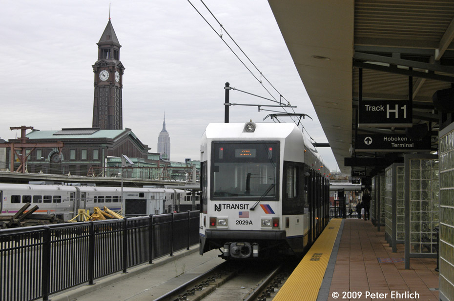 (189k, 930x618)<br><b>Country:</b> United States<br><b>City:</b> Hoboken, NJ<br><b>System:</b> Hudson Bergen Light Rail<br><b>Location:</b> Hoboken <br><b>Car:</b> NJT-HBLR LRV (Kinki-Sharyo, 1998-99)  2029 <br><b>Photo by:</b> Peter Ehrlich<br><b>Date:</b> 10/9/2009<br><b>Notes:</b> With station tower and Empire State Building in the background.<br><b>Viewed (this week/total):</b> 0 / 133