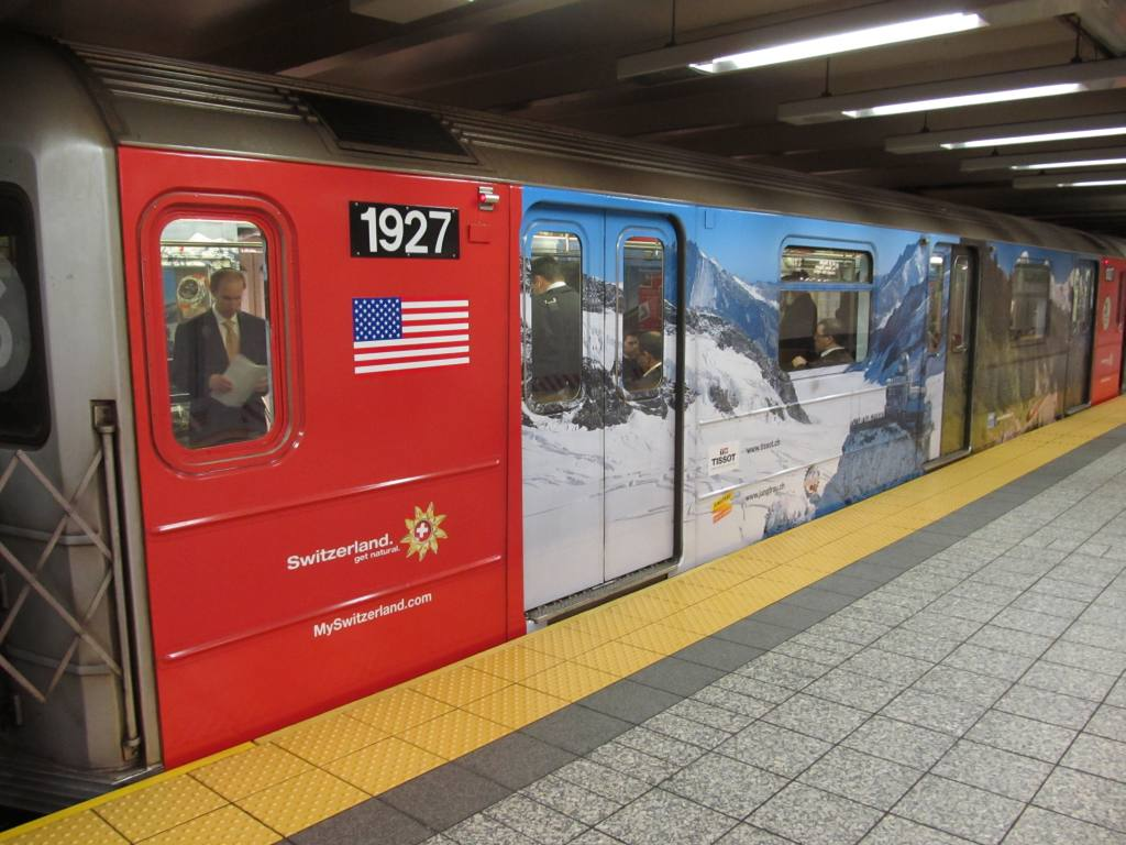 (114k, 1024x768)<br><b>Country:</b> United States<br><b>City:</b> New York<br><b>System:</b> New York City Transit<br><b>Line:</b> IRT Times Square-Grand Central Shuttle<br><b>Location:</b> Grand Central <br><b>Route:</b> S<br><b>Car:</b> R-62A (Bombardier, 1984-1987)  1927 <br><b>Photo by:</b> Robbie Rosenfeld<br><b>Date:</b> 5/3/2012<br><b>Notes:</b> Switzerland tourism ad wrap<br><b>Viewed (this week/total):</b> 0 / 190