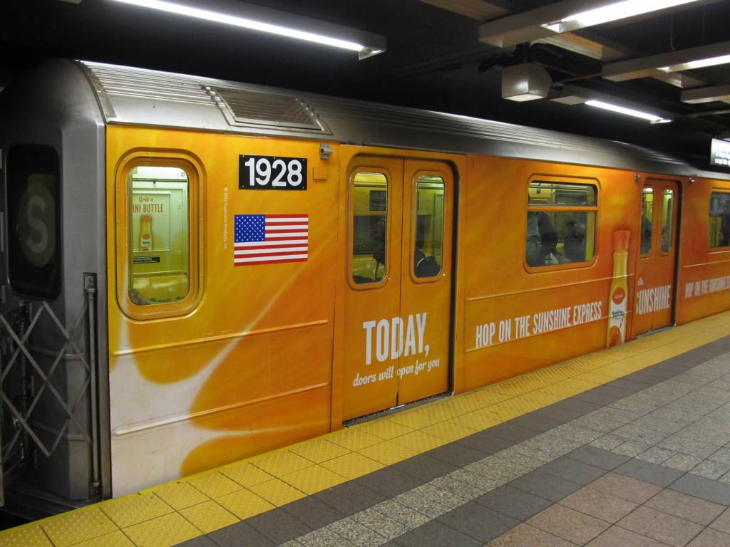 (114k, 1024x768)<br><b>Country:</b> United States<br><b>City:</b> New York<br><b>System:</b> New York City Transit<br><b>Line:</b> IRT Times Square-Grand Central Shuttle<br><b>Location:</b> Grand Central <br><b>Route:</b> S<br><b>Car:</b> R-62A (Bombardier, 1984-1987)  1928 <br><b>Photo by:</b> Robbie Rosenfeld<br><b>Date:</b> 1/21/2013<br><b>Notes:</b> Tropicana Orange Juice ad wrap<br><b>Viewed (this week/total):</b> 0 / 227