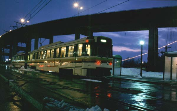 (58k, 600x378)<br><b>Country:</b> United States<br><b>City:</b> Buffalo, NY<br><b>System:</b> NFTA-Metro<br><b>Photo by:</b> Rob Hutchinson<br><b>Date:</b> 2/2001<br><b>Notes:</b> A two car train lays over at the 'Special Event' station, just south of Auditorium.  This station serves only the HSBC arena and is only open for Sabres games.  The row of lights on the right of the picture are on a battleship that is docked for display.<br><b>Viewed (this week/total):</b> 10 / 8018