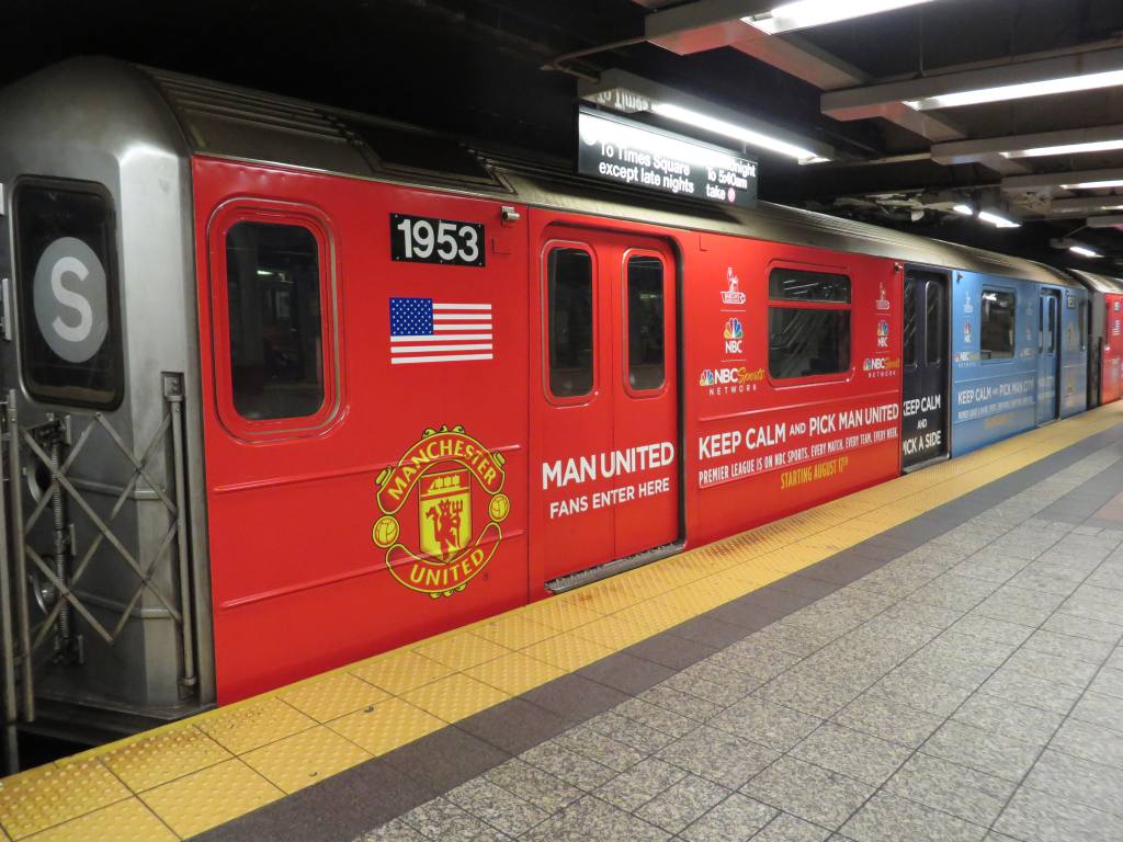 (128k, 1024x768)<br><b>Country:</b> United States<br><b>City:</b> New York<br><b>System:</b> New York City Transit<br><b>Line:</b> IRT Times Square-Grand Central Shuttle<br><b>Location:</b> Grand Central <br><b>Route:</b> S<br><b>Car:</b> R-62A (Bombardier, 1984-1987)  1953 <br><b>Photo by:</b> Robbie Rosenfeld<br><b>Date:</b> 8/11/2013<br><b>Notes:</b> NBC sports soccer wrap.<br><b>Viewed (this week/total):</b> 0 / 779