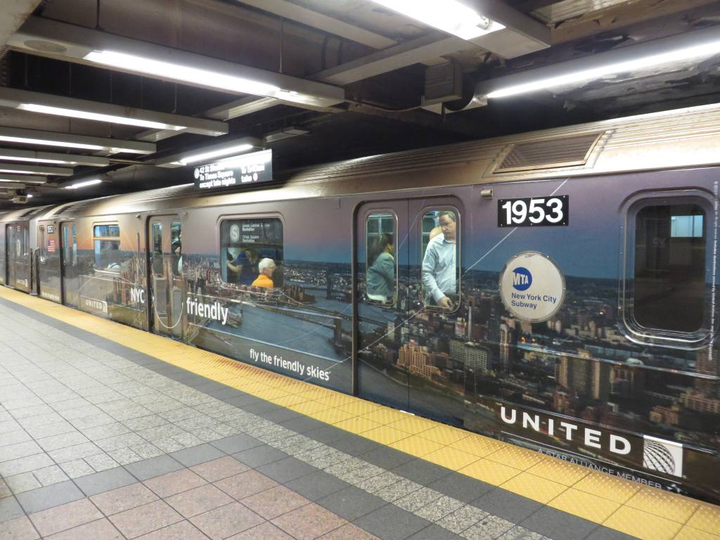 (132k, 1024x768)<br><b>Country:</b> United States<br><b>City:</b> New York<br><b>System:</b> New York City Transit<br><b>Line:</b> IRT Times Square-Grand Central Shuttle<br><b>Location:</b> Grand Central <br><b>Route:</b> S<br><b>Car:</b> R-62A (Bombardier, 1984-1987)  1953 <br><b>Photo by:</b> Robbie Rosenfeld<br><b>Date:</b> 10/3/2013<br><b>Notes:</b> United ad wrap<br><b>Viewed (this week/total):</b> 0 / 353