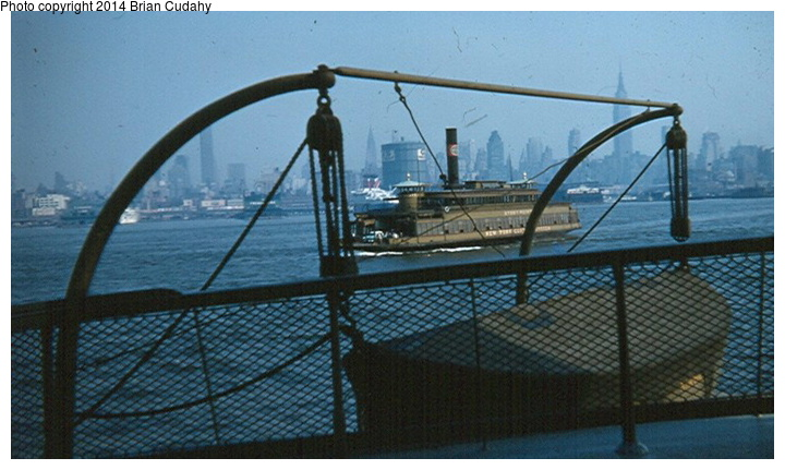(138k, 720x431)<br><b>Country:</b> United States<br><b>System:</b> New York Central <br><b>Photo by:</b> Brian J. Cudahy<br><b>Notes:</b> Seen from the upper deck of a NYC ferryboat, another boat makes its way across the Hudson to Weehawken. Ocean liner in the background is the SS United States. 1959.<br><b>Viewed (this week/total):</b> 23 / 928