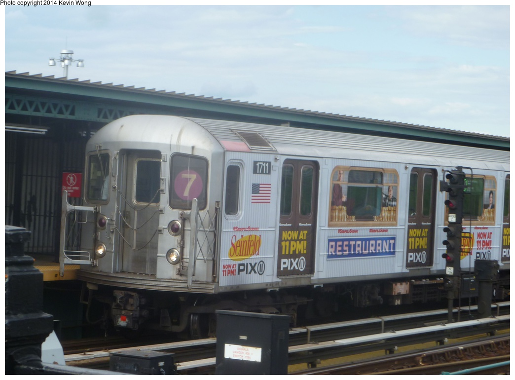 (238k, 1044x770)<br><b>Country:</b> United States<br><b>City:</b> New York<br><b>System:</b> New York City Transit<br><b>Line:</b> IRT Flushing Line<br><b>Location:</b> Willets Point/Mets (fmr. Shea Stadium) <br><b>Route:</b> 7<br><b>Car:</b> R-62A (Bombardier, 1984-1987)  1711 <br><b>Photo by:</b> Kevin Wong<br><b>Date:</b> 5/18/2014<br><b>Notes:</b> Seinfeld ad wrap<br><b>Viewed (this week/total):</b> 0 / 246