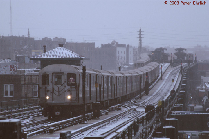 (110k, 720x478)<br><b>Country:</b> United States<br><b>City:</b> New York<br><b>System:</b> New York City Transit<br><b>Line:</b> IRT Flushing Line<br><b>Location:</b> 69th Street/Fisk Avenue <br><b>Route:</b> 7<br><b>Car:</b> R-62A (Bombardier, 1984-1987)  1681 <br><b>Photo by:</b> Peter Ehrlich<br><b>Date:</b> 3/6/2003<br><b>Notes:</b> Triple R62A scene in the snow.  1681 is leading a Flushing line express, which is about to pass 69th Street/Fisk Avenue station. A Flushing-bound local and an inbound train are visible at Woodside station.<br><b>Viewed (this week/total):</b> 12 / 4697