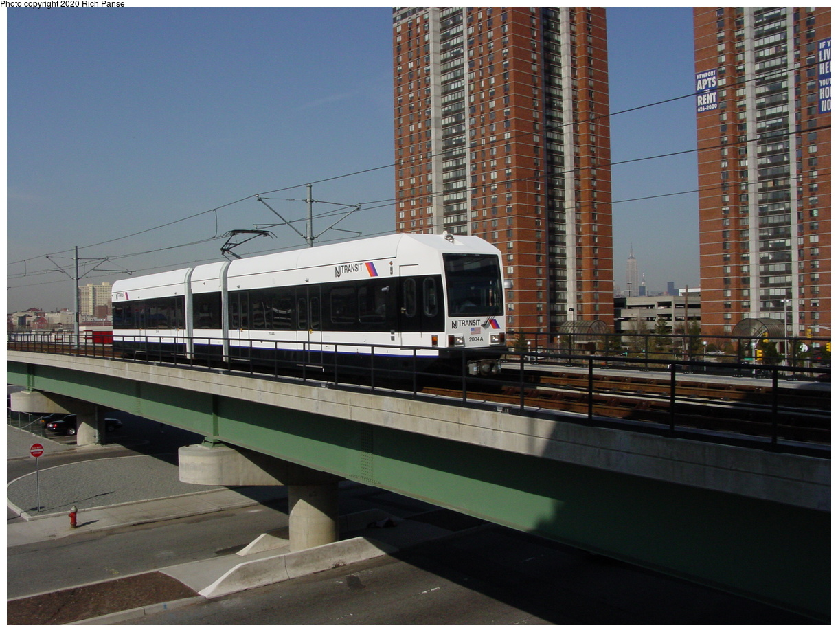 (66k, 768x576)<br><b>Country:</b> United States<br><b>City:</b> Jersey City, NJ<br><b>System:</b> Hudson Bergen Light Rail<br><b>Location:</b> Pavonia/Newport <br><b>Car:</b> NJT-HBLR LRV (Kinki-Sharyo, 1998-99)   <br><b>Photo by:</b> Richard Panse<br><b>Date:</b> 2003<br><b>Notes:</b> Overpass crossing Newport Parkway, view from parking deck<br><b>Viewed (this week/total):</b> 0 / 3393