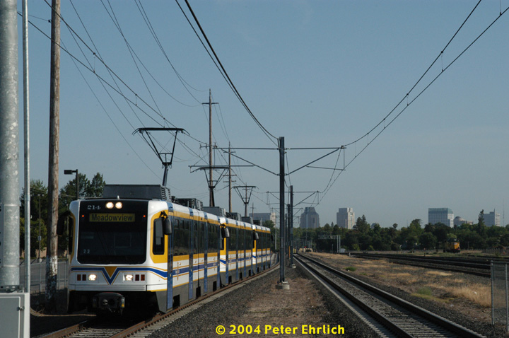 (129k, 720x478)<br><b>Country:</b> United States<br><b>City:</b> Sacramento, CA<br><b>System:</b> SACRT Light Rail<br><b>Location:</b> City College <br><b>Car:</b> Sacramento CAF LRV  214 <br><b>Photo by:</b> Peter Ehrlich<br><b>Date:</b> 6/28/2004<br><b>Notes:</b> A 3-car outbound train approaching City College Station, with the downtown skyline, and a Union Pacific locomotive, in the background.<br><b>Viewed (this week/total):</b> 1 / 1162