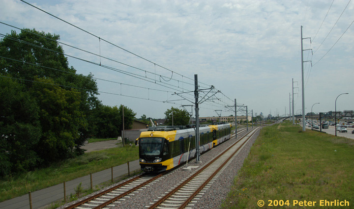 (128k, 720x426)<br><b>Country:</b> United States<br><b>City:</b> Minneapolis, MN<br><b>System:</b> MNDOT Light Rail Transit<br><b>Line:</b> Hiawatha Line<br><b>Location:</b> South of Franklin Avenue <br><b>Car:</b> Bombardier Flexity Swift  112 <br><b>Photo by:</b> Peter Ehrlich<br><b>Date:</b> 8/2/2004<br><b>Notes:</b> South of the pedestrian bridge, the line goes onto a viaduct to cross bustling Route 55, which is the numeric line designation for the Hiawatha LRT.<br><b>Viewed (this week/total):</b> 1 / 2052