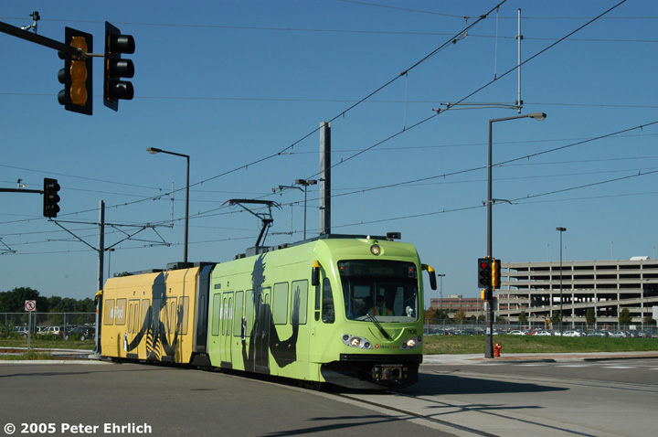 (120k, 720x478)<br><b>Country:</b> United States<br><b>City:</b> Minneapolis, MN<br><b>System:</b> MNDOT Light Rail Transit<br><b>Line:</b> Hiawatha Line<br><b>Location:</b> <b><u>28th Ave. </b></u><br><b>Car:</b> Bombardier Flexity Swift  110 <br><b>Photo by:</b> Peter Ehrlich<br><b>Date:</b> 8/27/2005<br><b>Notes:</b> Inbound train at the 28th Avenue/82nd Street intersection just beyond 28th Avenue Station.  110 is one of at least three LRVs shrinkwrapped with iPod adverts.<br><b>Viewed (this week/total):</b> 0 / 1154