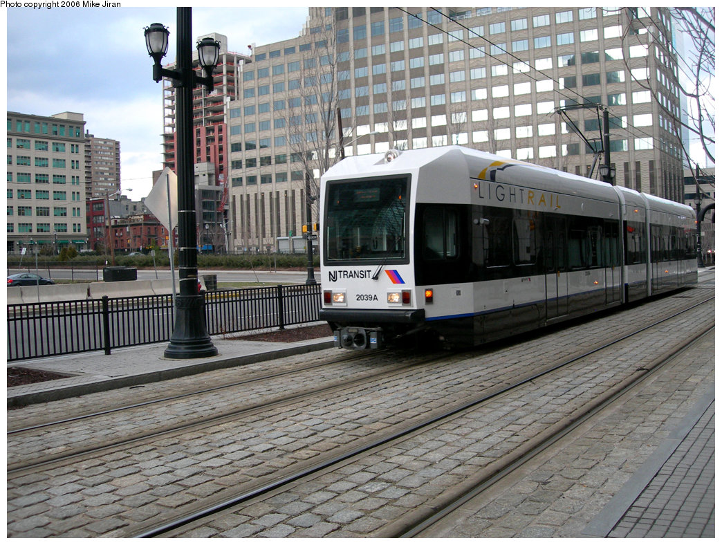 (296k, 1044x788)<br><b>Country:</b> United States<br><b>City:</b> Jersey City, NJ<br><b>System:</b> Hudson Bergen Light Rail<br><b>Location:</b> Exchange Place <br><b>Car:</b> NJT-HBLR LRV (Kinki-Sharyo, 1998-99)  2039 <br><b>Photo by:</b> Mike Jiran<br><b>Date:</b> 2/5/2006<br><b>Notes:</b> New car 2039 with new logo.<br><b>Viewed (this week/total):</b> 0 / 1530