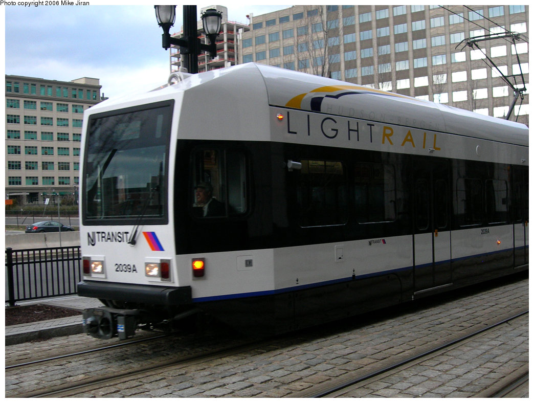 (221k, 1044x788)<br><b>Country:</b> United States<br><b>City:</b> Jersey City, NJ<br><b>System:</b> Hudson Bergen Light Rail<br><b>Location:</b> Exchange Place <br><b>Car:</b> NJT-HBLR LRV (Kinki-Sharyo, 1998-99)  2039 <br><b>Photo by:</b> Mike Jiran<br><b>Date:</b> 2/5/2006<br><b>Notes:</b> New car 2039 with new logo.<br><b>Viewed (this week/total):</b> 2 / 1673
