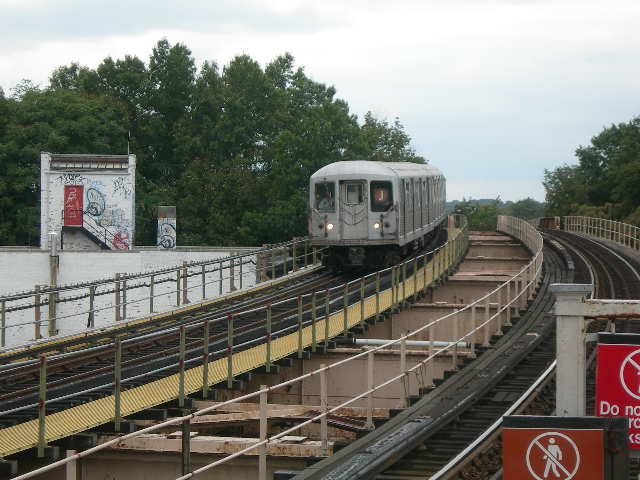 (80k, 640x480)<br><b>Country:</b> United States<br><b>City:</b> New York<br><b>System:</b> New York City Transit<br><b>Line:</b> BMT Nassau Street/Jamaica Line<br><b>Location:</b> 102nd-104th Streets <br><b>Photo by:</b> Joe Grillo<br><b>Date:</b> 9/10/2006<br><b>Notes:</b> J eastbound pulling into 104th street BMT station. The tall trees to the left is the old Brooklyn Manor LIRR right of way and station.<br><b>Viewed (this week/total):</b> 2 / 2292