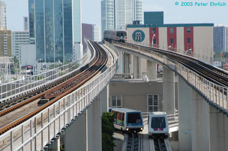(162k, 792x526)<br><b>Country:</b> United States<br><b>City:</b> Miami, FL<br><b>System:</b> Miami Metromover<br><b>Location:</b> Government Center <br><b>Car:</b>  2/25 <br><b>Photo by:</b> Peter Ehrlich<br><b>Date:</b> 4/25/2003<br><b>Notes:</b> Two cars pass south of Government Center Station.  Southbound Metrorail train in background.<br><b>Viewed (this week/total):</b> 0 / 2354