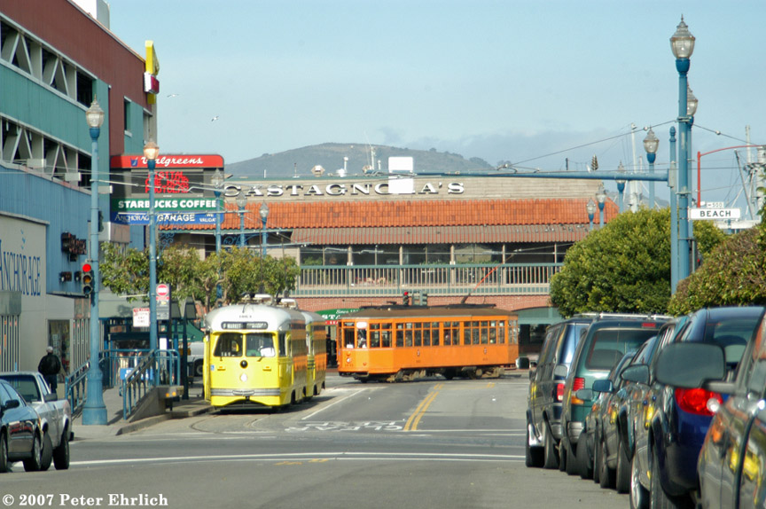 (208k, 864x574)<br><b>Country:</b> United States<br><b>City:</b> San Francisco/Bay Area, CA<br><b>System:</b> SF MUNI<br><b>Location:</b> Jones/Beach <br><b>Car:</b> SF MUNI PCC (Ex-SEPTA) (St. Louis Car Co., 1947-1948)  1063/1057 <br><b>Photo by:</b> Peter Ehrlich<br><b>Date:</b> 1/10/2007<br><b>Notes:</b> Baltimore, Cincinnati livery PCC cars, viewed from Jones/North Point. With Milan 1915 arriving terminal.<br><b>Viewed (this week/total):</b> 0 / 701