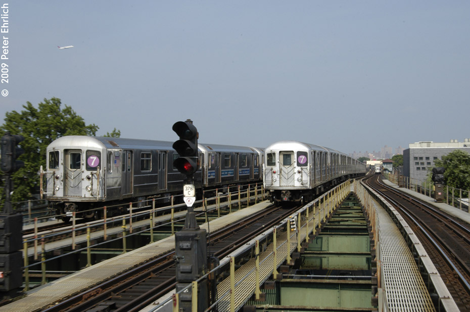 (184k, 930x618)<br><b>Country:</b> United States<br><b>City:</b> New York<br><b>System:</b> New York City Transit<br><b>Line:</b> IRT Flushing Line<br><b>Location:</b> Junction Boulevard <br><b>Route:</b> 7<br><b>Car:</b> R-62A (Bombardier, 1984-1987)  1820 <br><b>Photo by:</b> Peter Ehrlich<br><b>Date:</b> 7/22/2009<br><b>Notes:</b> Inbound. With outbound express leaving, and outbound local at 103rd Street in the background.<br><b>Viewed (this week/total):</b> 3 / 1039