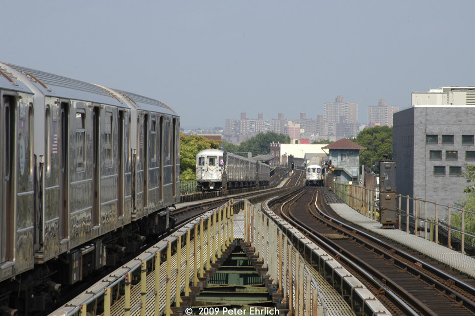 (203k, 930x618)<br><b>Country:</b> United States<br><b>City:</b> New York<br><b>System:</b> New York City Transit<br><b>Line:</b> IRT Flushing Line<br><b>Location:</b> Junction Boulevard <br><b>Route:</b> 7<br><b>Car:</b> R-62A (Bombardier, 1984-1987)  2064 <br><b>Photo by:</b> Peter Ehrlich<br><b>Date:</b> 7/22/2009<br><b>Notes:</b> Outbound. With inbound local approaching Junction Blvd., and an outbound local at 103rd Street in the background.<br><b>Viewed (this week/total):</b> 3 / 426